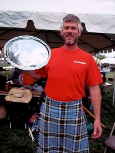 Lowell Thompson sports his Clan Thompson tee-shirt and the silver plate awarded him as best athlete overall at the festival.